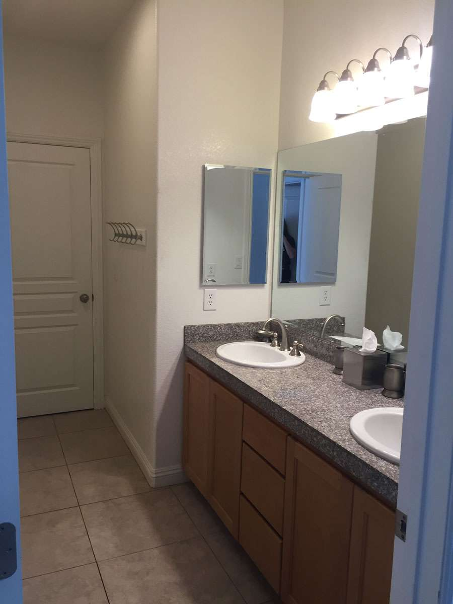 A shared full bath with separate room for double vanity