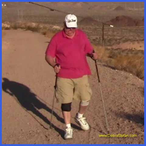 Trekking Poles- elderly man eases joints walking with trekking poles.